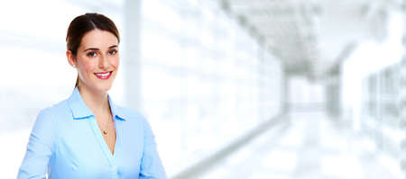 Beautiful young business woman over blue office background. Stock fotó