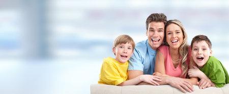 Familia feliz con los niños sobre fondo azul abstracto. Foto de archivo