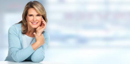 青い背景に美しい年配の女性の肖像画。