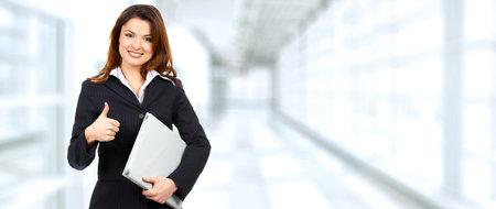 Mooie jonge vrouw op blauwe achtergrond kantoor. Stockfoto