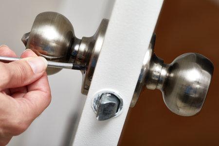 Les mains avec la fixation tournevis une serrure de porte. Banque d'images