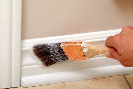 Hand of painter with paintbrush painting moulding.