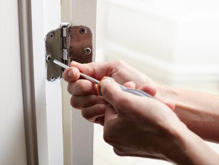 Hands with screwdriver fixing a door hinge. Foto de archivo