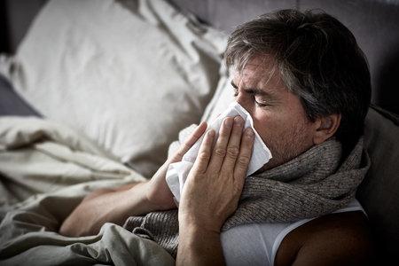 Zieke man met griep in bed lag en klap neus servet. Stockfoto