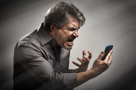 Angry roaring man with mobile phone. People rage expression.