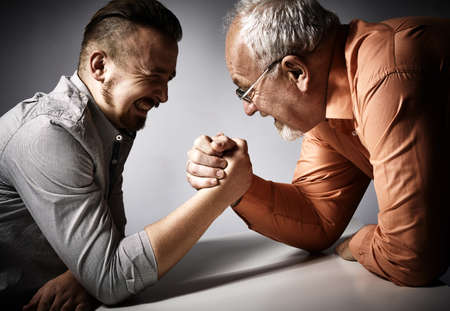 Two angry men arm wrestling competition on gray background.