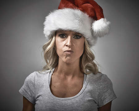 Angry Christmas girl in santa cap portrait.