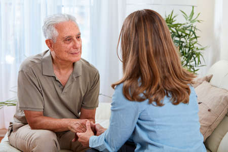 Old aged senior man talking with social worker woman at home.