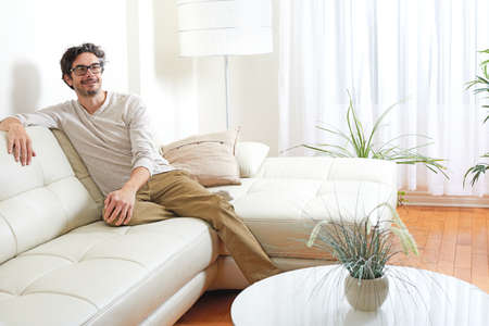 Handsome Man Relaxing At Cozy Modern Living Room Home. Stock Photo    64098429