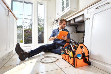 Loodgieter met tools doen herstel in de keuken.