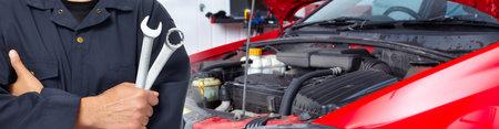 Mains de mécanicien automobile avec la clé dans le service de réparation automobile. Banque d'images - 64387065