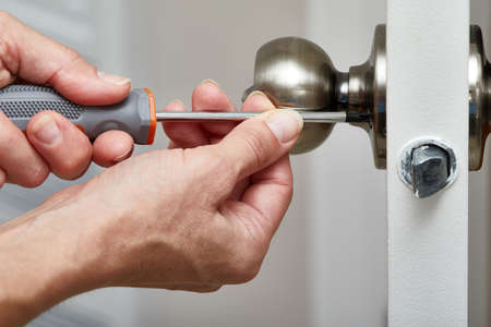 Mani con il fissaggio cacciavite una serratura.