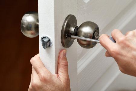 Hands with screwdriver fixing a door lock.