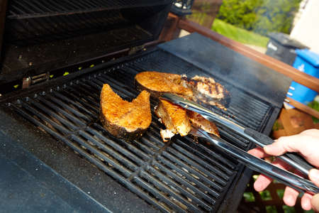 Fish cooking on hot barbecue grill. Summer vacation.