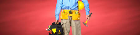 Construction worker with a tool belt over red background. Stock Photo