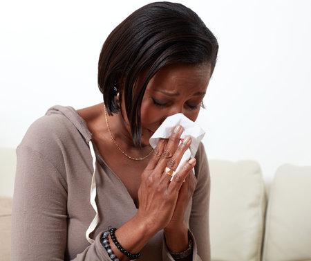 Afro-Amerikaanse vrouw blazen neus servet. Allergie gezondheidsproblemen Stockfoto