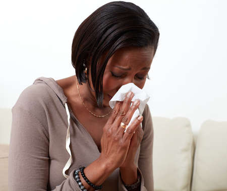 African-american woman blowing nose napkin. Allergy health problems.
