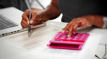 Hands of afro american accountant woman working with calculator. Imagens