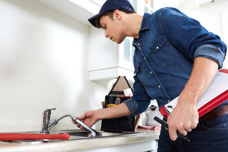 Professional plumber doing reparation in kitchen home. Banco de Imagens