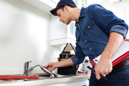Professionelle Klempner in der Küche zu Hause tun Wiedergutmachung. Standard-Bild - 64468121