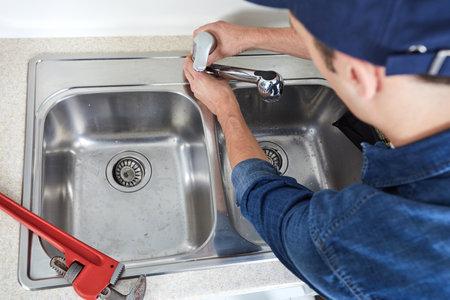 Professional plumber doing reparation in kitchen home. Standard-Bild