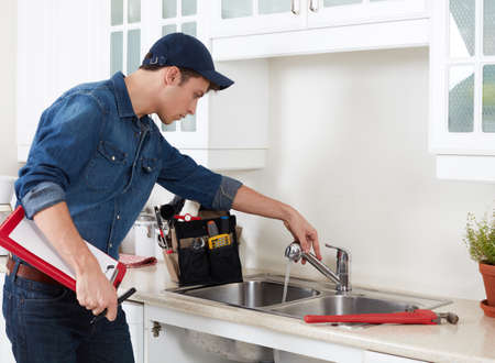 Professional plumber doing reparation in kitchen home. Stockfoto