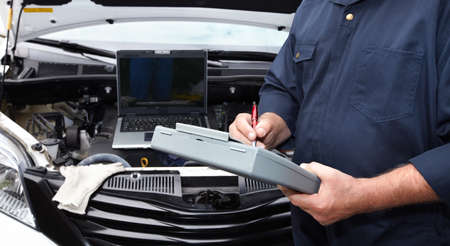 Ręki samochodowy mechanik z schowkiem w auto remontowej usługa. Zdjęcie Seryjne