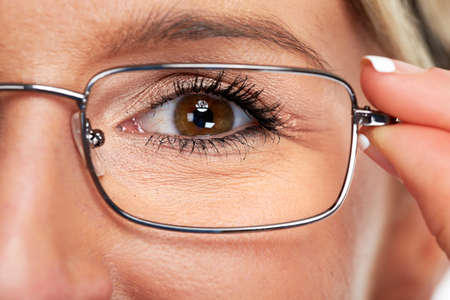 Young business woman face with eyeglasses eye health care background.