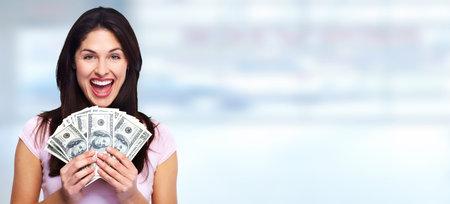 Szczęśliwa młoda uśmiechnięta kobieta trzyma gotówkę na niebieskim tle