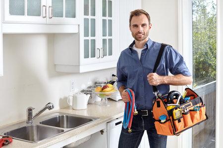 Plombier avec des outils faisant la réparation dans la cuisine. Banque d'images - 64969943