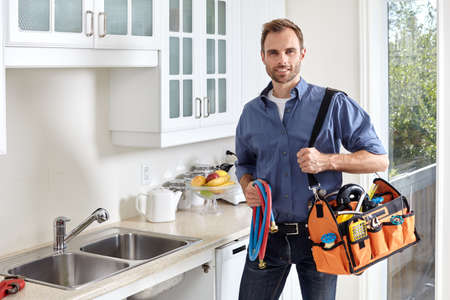 Plumber with tools doing reparation in the kitchen. Imagens