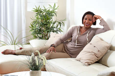 African-american woman sitting sofa at cozy apartment relaxing. Imagens