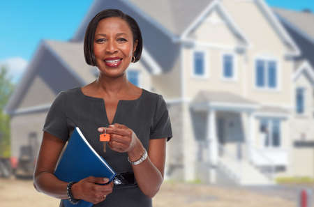 Smiling afro american real estate agent woman with house key. Foto de archivo