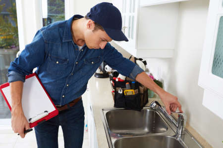 Professional plumber doing reparation in kitchen home.