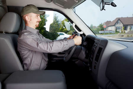 Young delivery man in a car. Transportation and shipping. Stock Photo