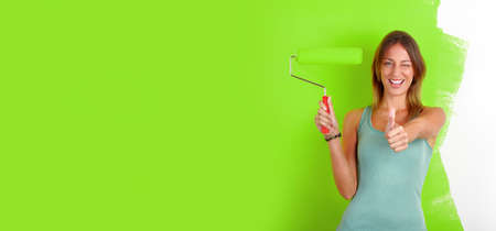 Happy smiling girl with painting roller near green wall background. Stock Photo