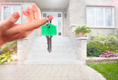 Woman hand giving house key. Real estate broker agent.