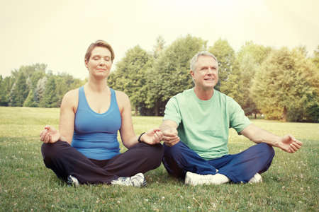 Happy healthy elderly couple yoga in the park.