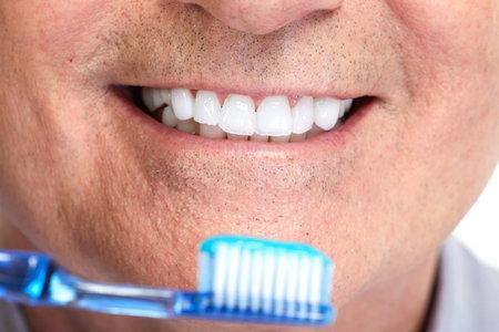 Guapo sonriente dientes con el cepillo de dientes maduros hombre