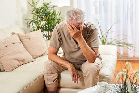 Elderly man at home having headache . Depression concept. Standard-Bild
