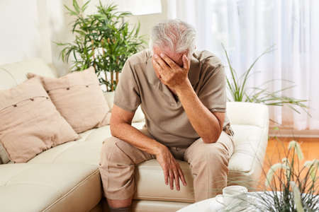 Elderly man at home having headache . Depression concept. Banco de Imagens