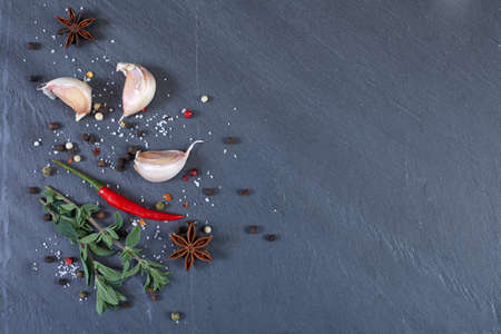 Herbs and spices on black stone surface background.