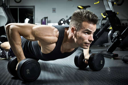 Strong young man exercising with dumbbells in gym. Sport Banco de Imagens