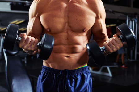 Strong young athletic man exercising dumbbell biceps workout