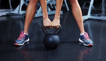 Athletic woman exercising with dumbbells in gym. Sport