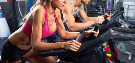 Group of people running on elliptical trainer