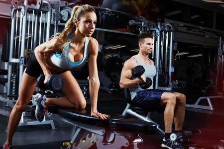 Sterke jonge atletische paar uitoefening gebogen over halter workout