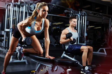 Strong young athletic couple exercising bent over dumbbell workout Stock Photo - 65806498