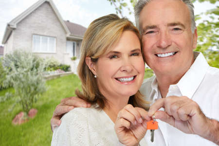 Smiling happy elderly couple holding house key.