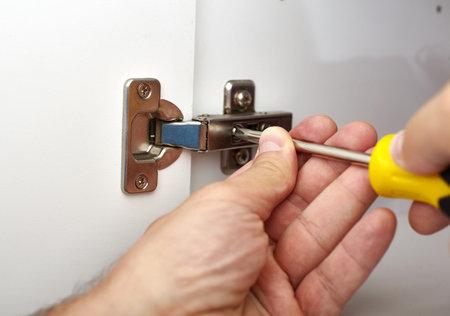 Hands with screwdriver fixing a door hinge. Standard-Bild